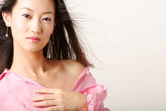Chinese girl. Enticing Chinese girl with flying hair in pink shirt royalty free stock photography