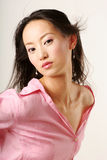 Chinese girl. Enticing Chinese girl with flying hair in pink shirt stock photography