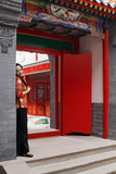 A Chinese girl. In traditional dress stands at the front door of the ancient courtyard of China Royalty Free Stock Photography