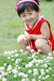 Chinese girl. The Chinese girl looking at the white flowers on the grassplot Stock Photo