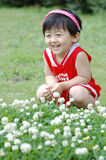 Chinese girl. The Chinese girl looking at the white flowers on the grassplot Royalty Free Stock Photos