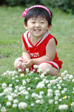 Chinese girl. The Chinese girl looking at the white flowers on the grassplot Royalty Free Stock Image