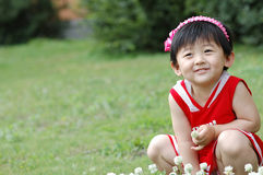 Chinese girl. The Chinese girl looking at the white flowers on the grassplot Royalty Free Stock Images