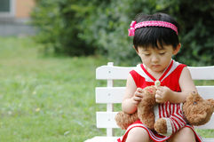 Chinese girl. The Chinese girl looking at the bear on the chair Royalty Free Stock Photos