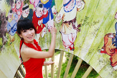 Chinese girl. A modern Chinese girl is being attracted by the old painting on the Chinese fan Stock Images