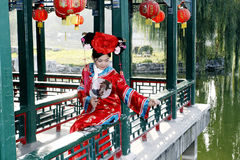 Chinese girl in ancient dress. A beautiful girl in Chinese ancient dress is sitting in the ancient long corridor of China Stock Images
