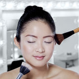 Chinese girl apply makeup brushes Stock Image
