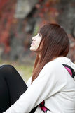 Chinese girl in autumn. Chinese girl sitting outside enjoying the autumn scenery Stock Photo