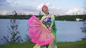 Chinese girl. Beautiful chinese girl in traditional chinese dress dancing with big pink fan on the riverbank stock video footage