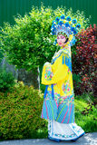 Chinese girl. Beautiful chinese girl in traditional chinese dress and hat standing outdoor Royalty Free Stock Photography
