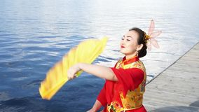 Chinese girl. Beautiful chinese girl in traditional red chinese dress with big yellow fan at the riverbank stock footage