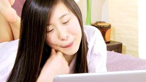 Chinese girl in bed playing with pc stock video
