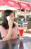 Chinese girl calling in cafe stock photo