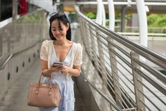 Chinese girl check shopping location by phone. Beautiful Chinese Tourist woman browsing map by 4g internet on smartphone to find shopping and travel location in Royalty Free Stock Image
