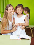 Chinese girl with child care worker. In kindergarten learning with a book Stock Photos
