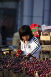 A Chinese girl is cleaning grapes for better sale Royalty Free Stock Images