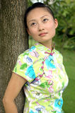 Chinese girl - dreaming. Chinese girl, romantic looks, dreaming and leaning on tree in park Royalty Free Stock Photos