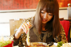 Chinese girl eating hot pot Stock Photography