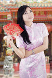 Chinese girl with envelope in the temple Royalty Free Stock Photo