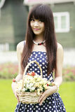Chinese girl with flowers. Chinese girl holding a basket of flowers smiling outdoor Royalty Free Stock Photos