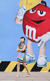 Chinese girl in front of large M&M`s billboard, Shanghai, China Stock Image