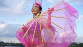 Chinese girl. Chinese geisha in traditional dress with big pink fan dancing outdoor stock footage