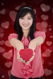 Chinese girl holds a gift with heart background Royalty Free Stock Photo