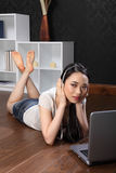 Chinese girl on internet with music in headphones Royalty Free Stock Photography
