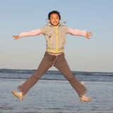 Chinese girl jumping on the sea Stock Photography