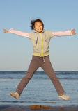 Chinese girl jumping on the sea Stock Photo