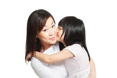 Chinese girl kissing asian mother against white. Long hair little chinese girl giving her mother a kiss on the cheeks Stock Image