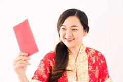 Chinese girl look at Ang pao envelope. Happy beautiful Chinese girl dress traditional cheongsam costume and look at ang pao money in red envelope on white Royalty Free Stock Image