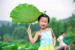 Chinese girl with lotus leaf hat Royalty Free Stock Images