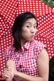 Chinese girl making a face with dotted umbrella Stock Images