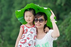 Chinese girl and mum with lotus leaf hat Stock Images