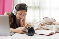 Chinese girl play smartphone on bed. Asian beautiful woman on bed listen online music vdo, play social media, and chat by smartphone. portrait of cute happy stock photo
