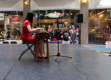 Chinese girl playing zither in mall. Vancouver, Canada, May 11, 2013 - a chinese girl playing zither in International Village mall Stock Images