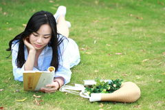 Chinese Girl reading the book. Blonde beautiful young woman with book lying on the grass. Stock Photo