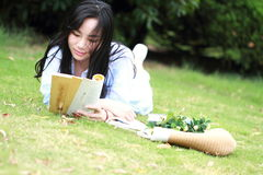 Chinese Girl reading the book. Blonde beautiful young woman with book lying on the grass. Royalty Free Stock Images