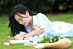 Chinese Girl reading the book. Blonde beautiful young woman with book lying on the grass. Stock Photos