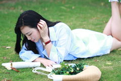 Chinese Girl reading the book. Blonde beautiful young woman with book lying on the grass. Stock Images