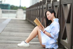 Chinese Girl reading book. Blonde beautiful young woman with book sit On the ground. Stock Image