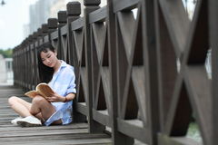 Chinese Girl reading book. Blonde beautiful young woman with book stand near fence. Royalty Free Stock Images