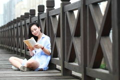 Chinese Girl reading book. Blonde beautiful young woman with book stand near fence. Stock Photography