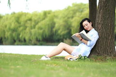 Chinese Girl reading a book under tree. Blonde beautiful young woman with book sit on the grass. Royalty Free Stock Photography