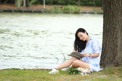 Chinese Girl reading a book under tree. Blonde beautiful young woman with book sit on the grass. Girl reading the book. Blonde beautiful young woman with book Royalty Free Stock Photography