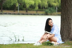 Chinese Girl reading a book under tree. Blonde beautiful young woman with book sit on the grass. Royalty Free Stock Photo