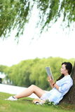Chinese Girl reading a book under tree. Blonde beautiful young woman with book sit on the grass. Stock Images
