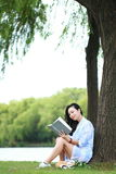 Chinese Girl reading a book under tree. Blonde beautiful young woman with book sit on the grass. Stock Photo