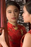 Chinese girl in red cheongsam by mirror. Portrait of young beautiful Chinese female in traditional clothes (cheongsam) standing by mirror Stock Images